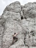 Young man climbing on limestone wall — 图库照片