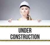 Worker holding under construction sign on information board — Stock Photo