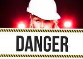 Worker holding danger sign on information board — Stock Photo