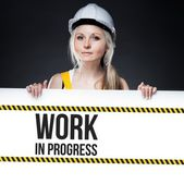 Work in progress sign on template board, worker woman — Stock Photo