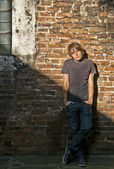 Handsome young man posing in front of brick wall — Stock Photo