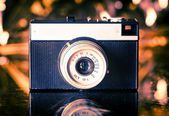 Old camera on gold background — Stock Photo
