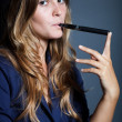 Elegant woman holding and smoking e cigarette — Stock Photo