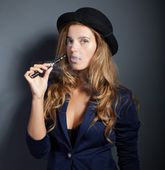Elegant woman smoking e-cigarette with smoke wearing suit and hat — Stock Photo
