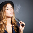 Elegant woman smoking e-cigarette with smoke wearing suit and hat — Stock Photo #31882399