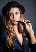 Elegant woman smoking e-cigarette wearing suit and hat — Stock Photo