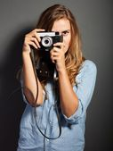 Photographer in jeans jacket taking pictures with old camera — Stock Photo