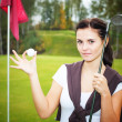 Woman golf player on green with ball and club near cup — Stock Photo #33727061
