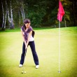 Woman golf player training putting ball on green to cup — Foto de Stock