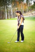 Woman golf player training on green with club — Stock Photo