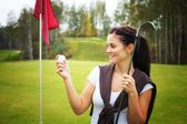 Young woman golf player looking at ball with club — Stockfoto