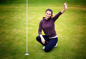Young woman golf player holding ball giving Thumbs Up sign — Stockfoto