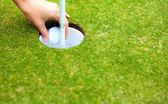 Player hand removing golf ball from cup after shot — Stock Photo