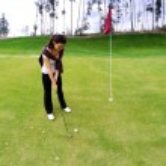 Young woman golf player on green, preparing to shot — Foto de Stock
