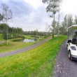 Golf course landscape with golf-cart car — Stock Photo