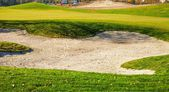 Sand bunker on the golf course with grass — Stockfoto