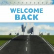 Welcome back road sign on highway in city — Stock Photo