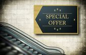 Moving escalator stairs with special offer — Stock Photo