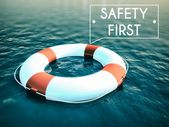 Safety First sign lifebuoy on rough water waves — Stock Photo