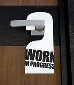 Door hanger Work in progress message on handle — Stock Photo