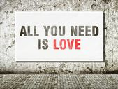 All you need is love, words on wall — Stockfoto