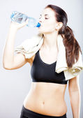 Young natural woman drinking water after fitness training — Stock Photo