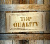 Stamp Top Quality label old wooden box — Stock Photo