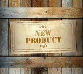 Stamp New Product label old wooden box — Stock Photo