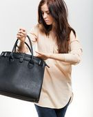 Elegant young woman looking in her purse — Stockfoto