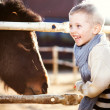 Smiling child with pony in mini zoo — Stock Photo #44422917