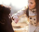 Young woman stroking pony in mini zoo — Stock Photo