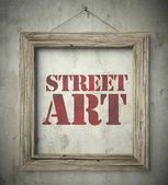 Street art in old wooden frame on wall — Stock Photo