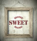 Home sweet home emblem in old wooden frame — Stock Photo