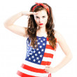 Pin up girl wrapped in american flag saluting — Stock Photo #47375301