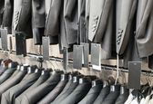 Row of elegant suits jacket on hangers, apparel store — Stock Photo