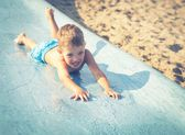 Child on water slide at aquapark, summer holiday — Stock Photo