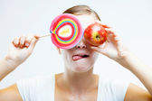 Woman choosing between sweets and fruits — Stock Photo