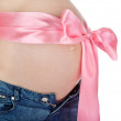 Stock Photo: Abdomen a young pregnant woman with a pink ribbon.