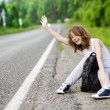 Young tourist hitchhiking along a road. — Stock Photo