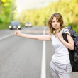 Young woman hitchhiking along a road — Stock Photo