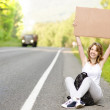 Beautiful young female hitchhiker with cardboard — Stock Photo