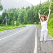 Beautiful woman hitch hiking on an asphalt road — Stock Photo