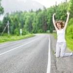 Beautiful woman hitch hiking on an asphalt road — Stock Photo