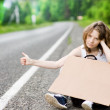 Sad girl hitchhiking along a road with message board - Stock Photo