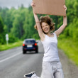 Stock Photo: Young tourist hitchhiking along a road with message board