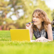 Young beautiful woman lies on green summer meadow with laptop — Stock Photo