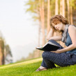 Young nice attentive woman sitting on green grass and reads book — Stock Photo