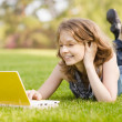 Stock Photo: College student lying down on grass working on laptop at campus