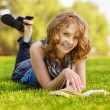 Charming girl lies on green grass and reads book. — Stock Photo