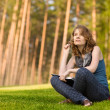 Stock Photo: Young beautiful womsitting on green grass and reads book